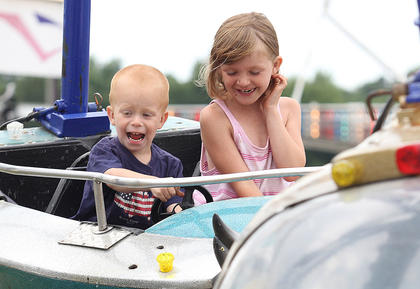 Kim Lee and Little John Mysinger enjoy a spin on one of the fair's many rides.