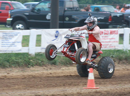 An ATV rider pops a wheelie as he speeds down the track during the KOI Drag Racing on July 2.