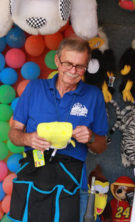 Pat Schroeck arranges some of the prizes at one of the game booths at the fair July 2.