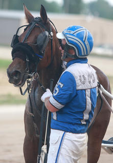 Tyler Shehan and Gliding Princess wait to pose for a winner's photo after the Simms Cut-Rate Liquors one-mile trot July 1 at the Marion County Fair.