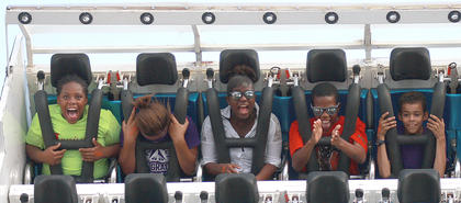 From left, Asia Cowherd (13), Jasmine Johnson (11), Asia Cowherd (13), Tyshay Epps (12) and Jashon Beam (8) take a ride on the Tsunami.