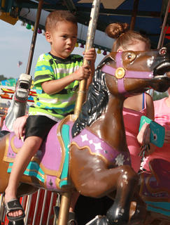 Xavier Harrington, 3, enjoys a spin on the merry-go-round.