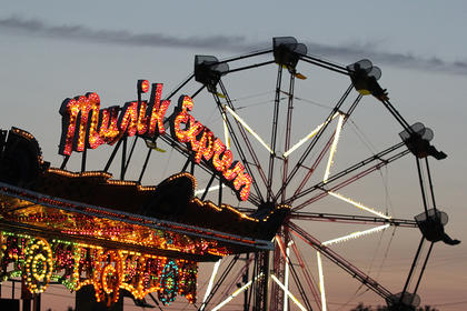 The lights of the carnival rides were more visible as the sun set.