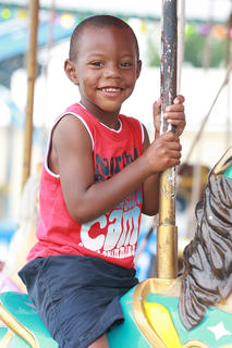 "Jatavion ""Munch"" Cowherd, 4, enjoys a ride on the merry-go-round."
