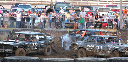 Spectators gathered around fences as close as they could to watch the demolition derby Friday evening.