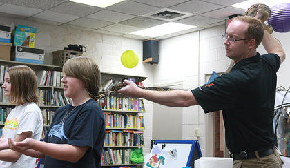 "Naturalist Michael Opferman of Animal Tales visited the Marion County Public Library Thursday and gave a presentation about a variety of animals from Africa and South America. The presentation included an amphibian, an arachnid, a bird, a mammal and a snake. Opferman touches Cole Koenig's neck with the tail of ""Diego"", a red-tailed boa constrictor. Koenig did not turn around."