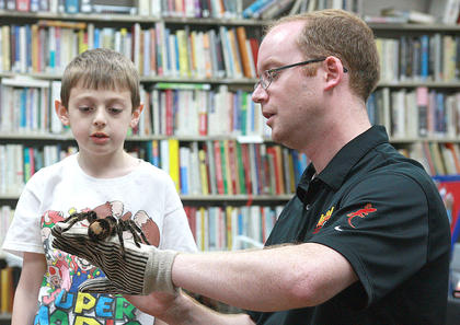 "Caleb Brown, left, helps Michael Opferman as he holds ""Charlotte,"" a Brazilian bird-eating tarantula."