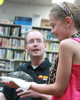 "Aubrey Mealey holds ""Prince Jabba,"" an African bullfrog, as Opferman explains why she shouldn't kiss the frog."