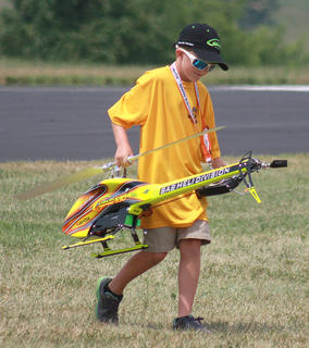 """Flyin'"" Ryan Robertson, 8, of Mt. Washington recovers his helicopter after performing an aerobatic routine with his helicopter during the opening ceremony. Robertson has been flying remote control aircraft since he was 3 years old."