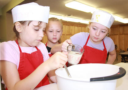 Amber Perkins mixes the ingredients for homemade biscuits as Alaura McCarty prepares to add some milk to the mix. Michaela Hutchins watches.