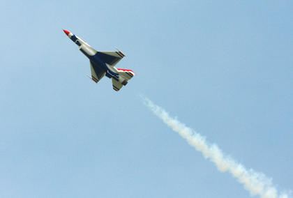 A military-style jet leaves a smoke trail as it makes a pass.