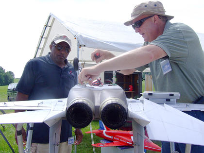 Randy Desrosiers, right, of Waterford, Mich., works on his plane between flights.
