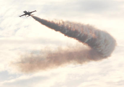 Friday evening, a jet releases smoke as it makes a turn during one of the final flights before sunset.