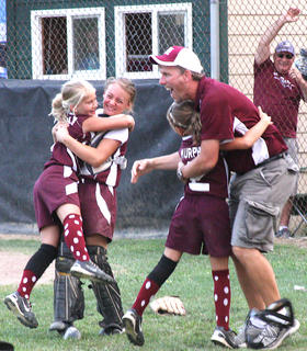 Assistant Coach Joe Pat Cecil hugs Addi Murphy as Haley Mattingly and Cassidy Logsdon embrace in celebration after winning the state championship.