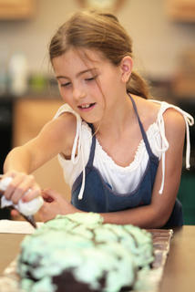 Cheyenne Raikes, 9, helps decorate a snake cake during the Marion County Arts and Humanities Council&#039;s summer camp was held July 11-15 at Lebanon Middle School and the Marion County Extension Office. Campers made jewelry, t-shirts, duct-tape wallets, pictures frames and food. They learned some new dance steps and played the drums, and throughout the week, they took pictures as well. 