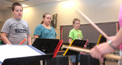 From left, Trevor Mudd, Kali Greene and Kendall Lupichino watch music instructor Sarah Martin. The drummers would then repeat what Martin had played.