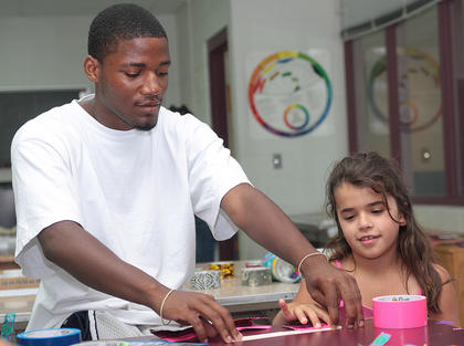 Volunteer Deshawn Douglas assists Gabbie Brockman, 8, in making her duct tape wallet.