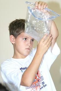 Gabe Hagan, 10, takes a closer look at the effect of a corn-based product on the absorption of water.