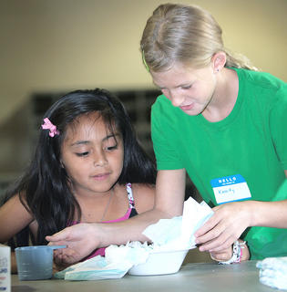 Aleli Huerta, 11, and Kassidy Mattingly, 10, watch as a diaper absorbs another half-cup of water.
