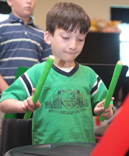 Benjamin Martin, 6, tries a new drumming technique.