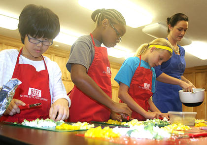 Pictured, from left, are Yuna Gorie, Daysa Spalding and Nicole Montgomery cutting up vegetables to be used in a chicken fajita recipe. Also pictured is FCS Agent Lizzie Spalding.