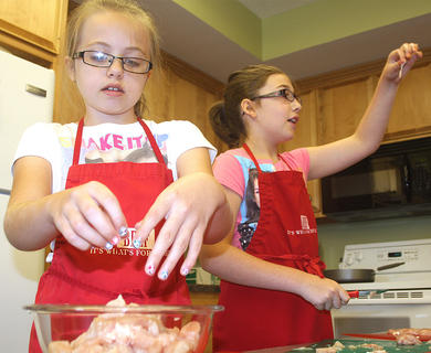 Cheyenne Mattingly and Alexia Lackey prepare chicken for a fajita recipe.