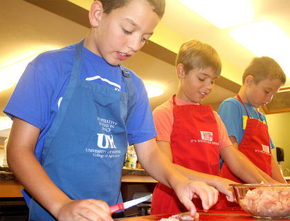From left, are Samuel Thompson, Landon Cambron, and Samuel Cambron cutting up chicken to use in a fajita recipe.