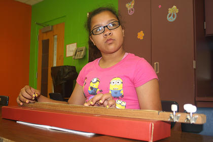 Riley Walker watches teacher Jessica Floyd for instruction as she plays the Appalachian dulcimer.