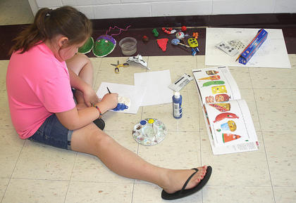 Chloe Murphy sits comfortably in the hallway at Lebanon Elementary School and works on her art project.