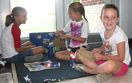 Maddie Wiser, Kalyee Reed and Maggie Benningfield share a laugh while they work on their art project.