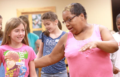 Dance instructor Mary Ester Furman helps Cheyenne Raikes with the Electric Slide. Morgan Tungate is in the background.