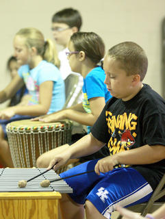 Nicholas Logsdon plays a xylophone during a music lesson.