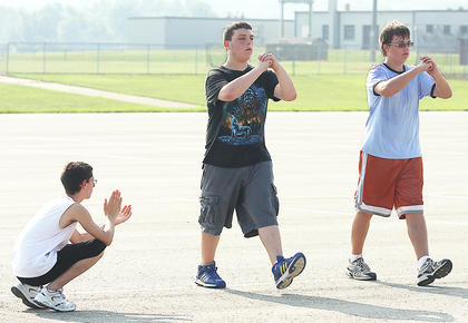 Alex Mann observes Anthony Chesser and Craig Deacon practice their steps to make sure they are correct.
