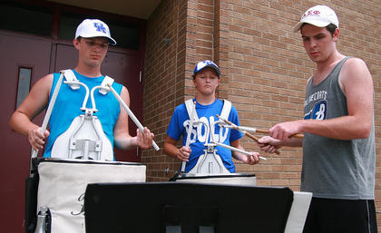 Sophomore Michael Richardson (left) and freshmen Elizabeth Hughes practice to serve as the drum line for this year's Marching Knights. Trent Fenwick (right), a Marching Knights alumni and band camp staff member, instructs them during band camp.