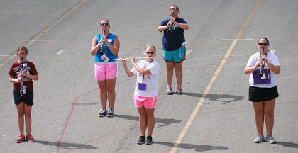 From left, seventh-grader Jessica Cambron, sophomore Melissa Clark, junior Kelsey Hamilton, sophomore Allison Sallee and junior Anne Kaitlyn Gribbins practice marching and playing in the woodwind section.
