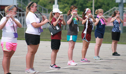 From left, junior Kelsey Hamilton, junior Anne Kaitlyn Gribbins, eighth-grader Breanna Morris, junior Lexi Cambron, freshman Maria Newton, freshman Gracie Cooper, and junior Lauran Knott work on learning the music and marching patter for the woodwinds.