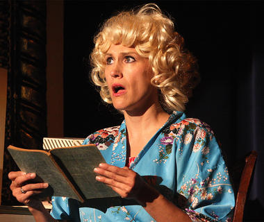 "Miss Adelaide, played by Robin Humphress, is distraught to find out that her fiancé, Nathan Detroit, is still running the crap game. She consults a medical book, which tells her that her chronic cold is a psychosomatic reaction to her frustration with Nathan's failure to marry her and sings ""Adelaide's Lament."""