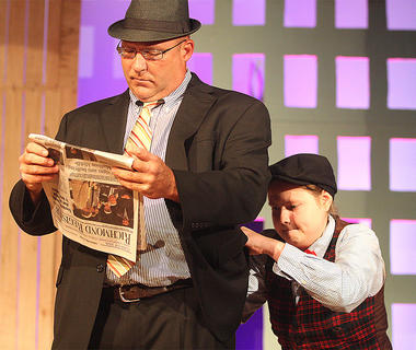 Rusty Blair, playing the part of Angie the Ox, reads the paper as Rachel Fitzpatrick, a pick pocket, steals his wallet.