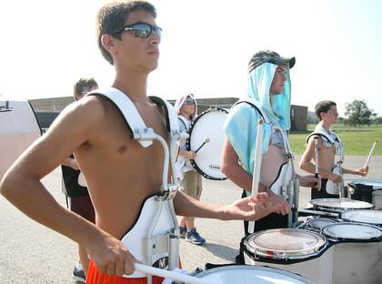 Drum corps members, from left, junior Zack Benningfield, senior Trent Fenwick and junior Alex Mann practice marching and playing.