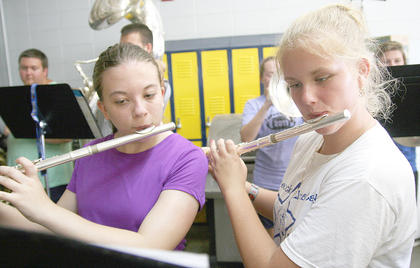 Freshmen Lauran Knott (left) and Kelsey Hamilton practice learning the music on the flute.