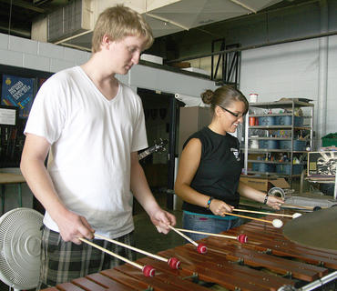 Instructor Michael Mather helps senior Kayti Dunn on the xylophone.
