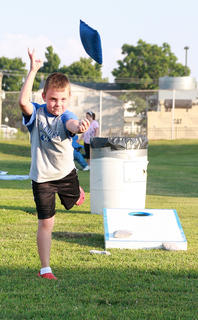 John Taylor, 6, tosses a bean bag at one of the cornhole boards set up for the event.