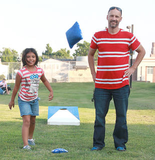 Lea O'Daniel, 5, and her dad, Robert, take turns playing cornhole.