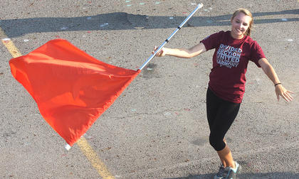 Color Guard member McKenna Bartley, freshman, smiles as she twirls her flag.