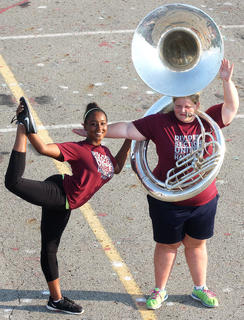 Color guard member Jarie Newby, junior, strikes a pose with Kate Cobb, sophomore, on the tuba.