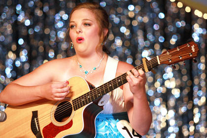 Ann Courtney Thompson strums her guitar and sings during the talent portion.