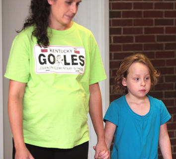 Jill Gaddie, a special education instructor, escorts Alisha Ewing, a kindergarten student, down the hall during the first day of school at Lebanon Elementary School.