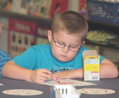 Trey Stine, 5, a kindergarten student at Lebanon Elementary, colors a coloring book page before class begins.