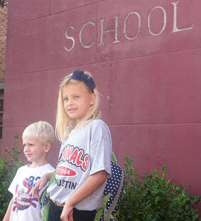St. Augustine second grader Nicole Montgomery and her brother Freddie, 4, pose for a photo before she enters the school on the first day.