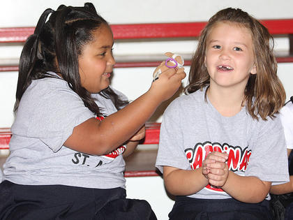 Angelina Parrott (left), 7, and Laci McCarty, 6, play around before classes start.